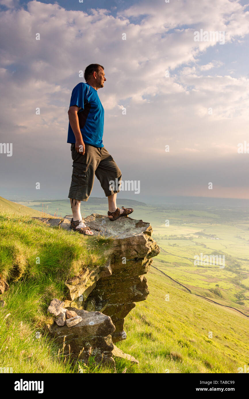 Man standing on rocky outcrop known as 'Nick's Chair' in the Forest of Bowland, Lancashire, UK - Stock Image