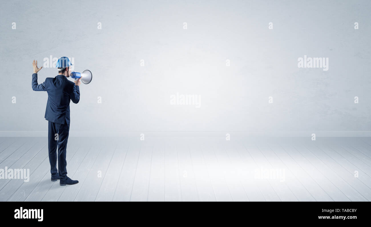 Young architect with construction helmet standing in an empty space and holding a plan  - Stock Image