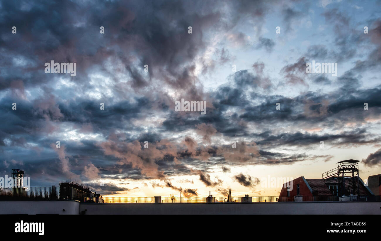 Dramatic cloudy evening sky over an apartment building rooftop at sunset in Mitte, Berlin Stock Photo