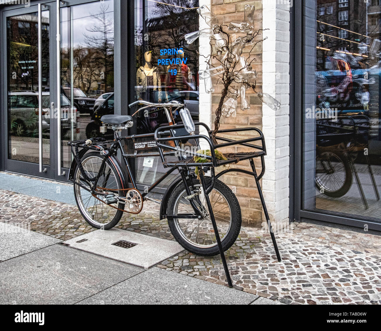 Berlin,Mitte, Ecoalf store display window and advertisement. Bicycle with tree of plastic bottles. Clothes made of recycled cotton & plastic bottles Stock Photo