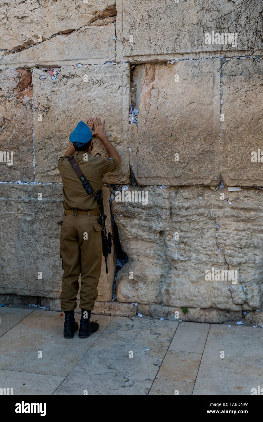 Jewish man prays next to a crack filled with letters containing written prayers at the Western Wall in Jerusalem. Israel - Stock Image