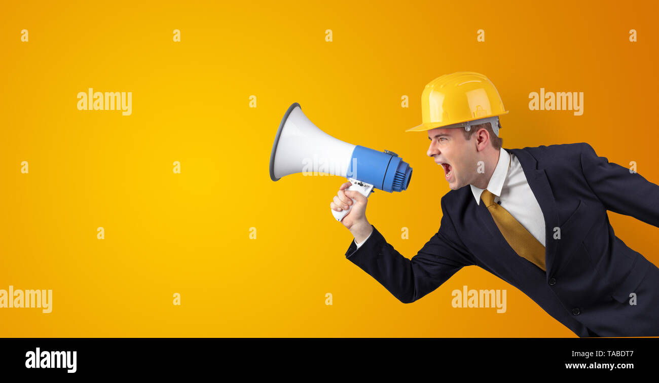 Young architect constructor yelling with megaphone and copyspace - Stock Image
