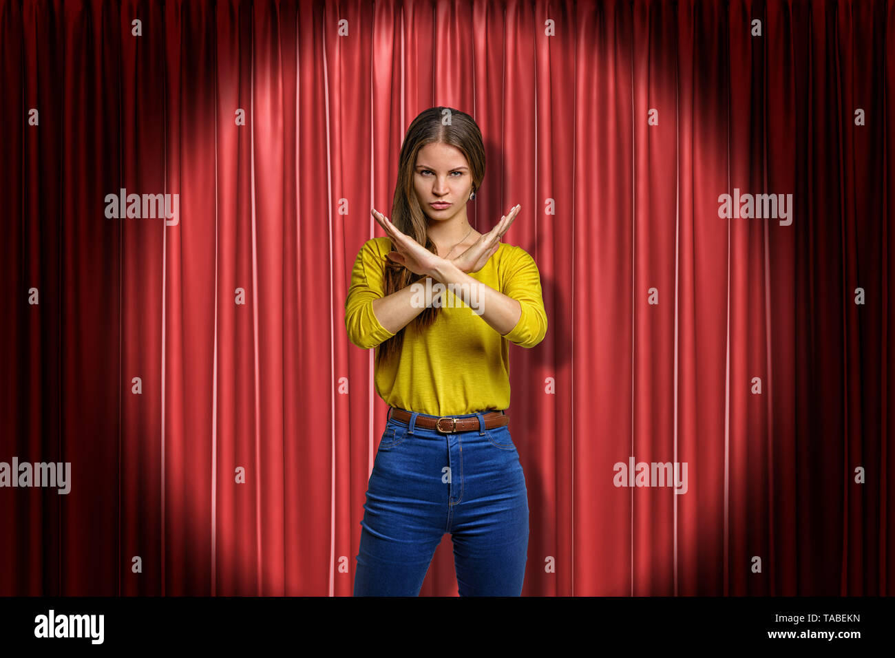 Young determined woman wearing jeans and yellow shirt making rejection gesture on red stage curtains background. Digital art. Feelings and emotions. P - Stock Image
