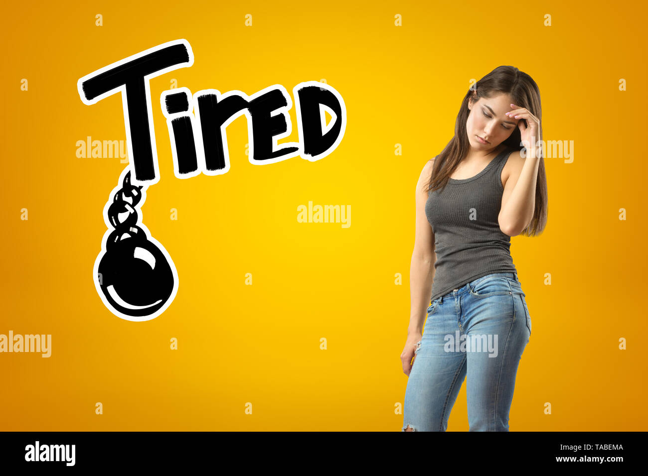 Young sad brunette girl wearing casual jeans and t-shirt with TIRED sign and black chained ball drawn on yellow background. Casual clothing. Feelings  - Stock Image