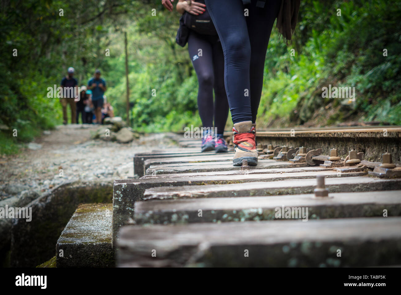 Hikers walking towards Machu Picchu from the hydroelectric power station, Peru - Stock Image
