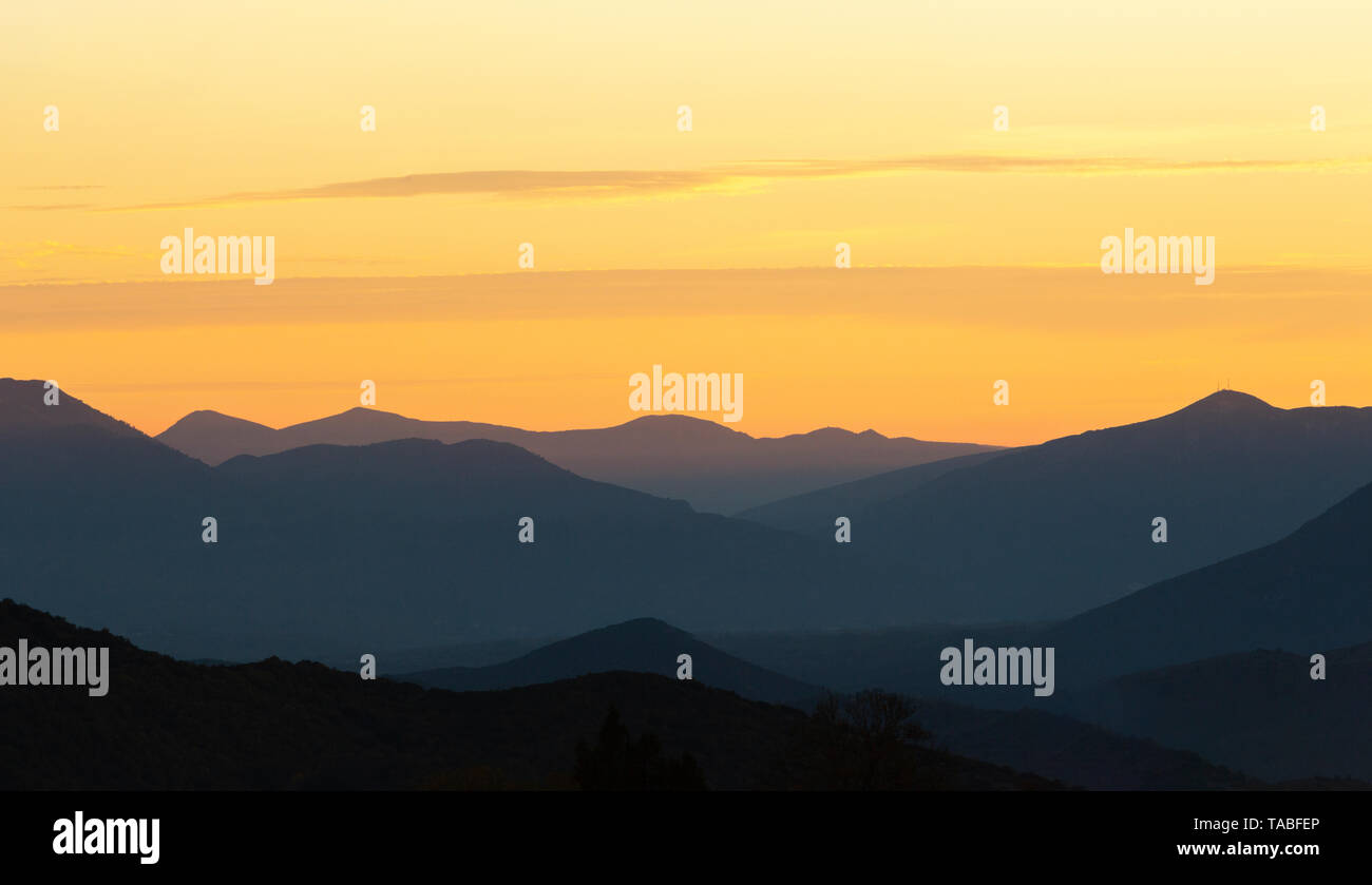 Hazy winter sunset in Pindus Mountains in Greece - Stock Image
