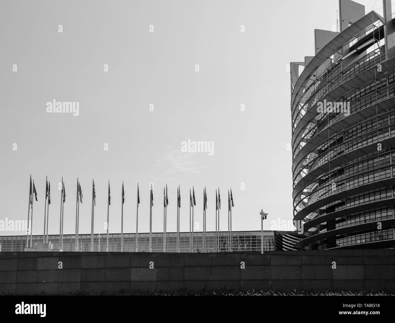 Side view of European Parliament headquarter in Strasbourg with all European union member flags waving and CCTV camera days before Parliamentary elections on 26 may - Stock Image