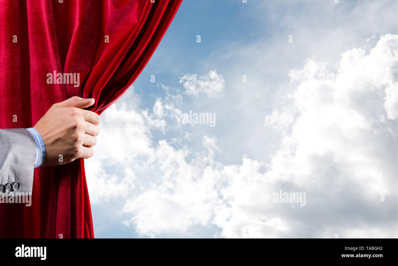 Cloudy landscape behind red curtain and hand holding it - Stock Image