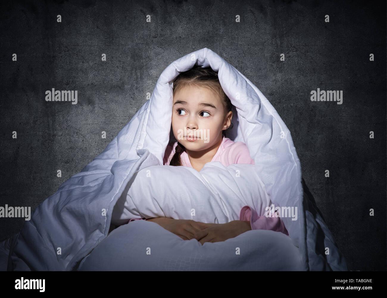 Frightened girl hiding under blanket - Stock Image