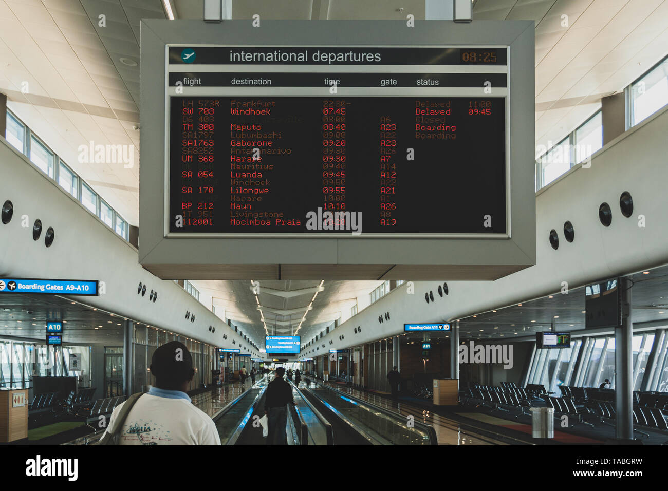 Man traveler passenger looks at flight schedule timetable board screen at terminal, O.R. Tambo International Airport, Johannesburg, South Africa - Stock Image