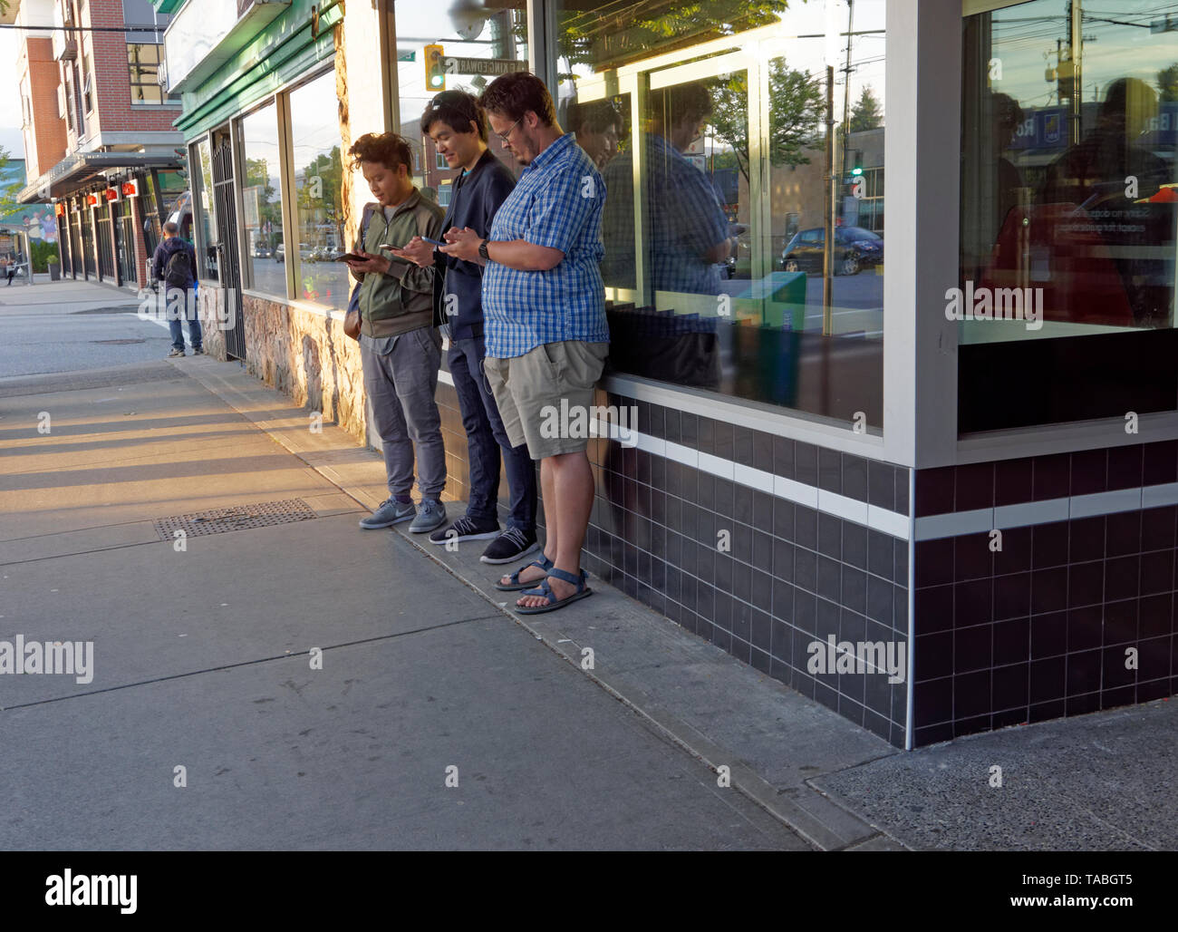 Three young men using their mobile cell phones while standing on the sidewalk, Main Street, Vancouver, BC, Canada - Stock Image