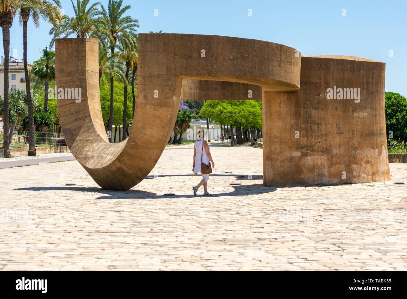 Woman walking though the geometric Tolerancia (Tolerance) monument, Seville, Andalusia region, Spain - Stock Image