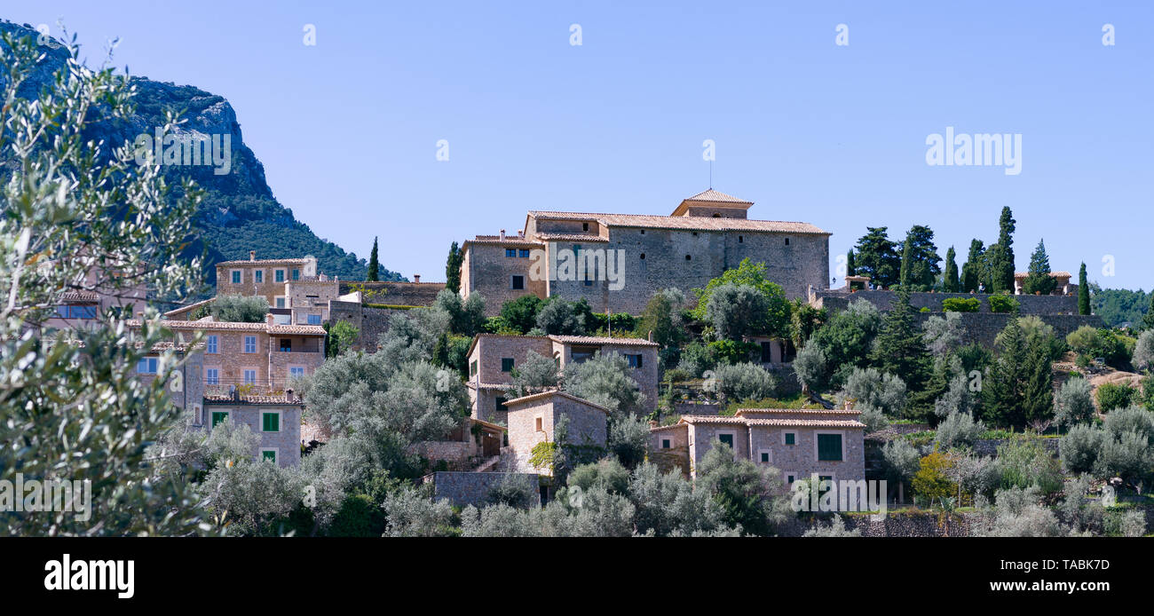 Low angle view of various buildings high on some rolling mountain terrain of Majorca. - Stock Image