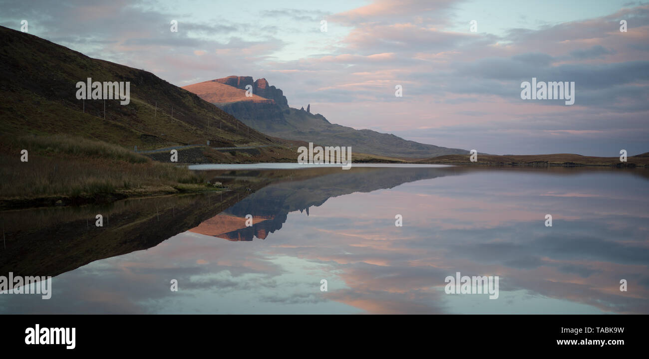 Peaceful and serene reflective view of rolling hills rising from a still lake. Stock Photo