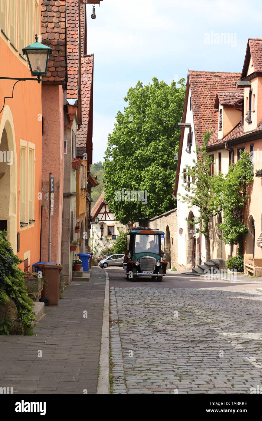 A little vehicle driving down a cobblestone road in Rothenburg ab der Tauber in southern Germany. - Stock Image