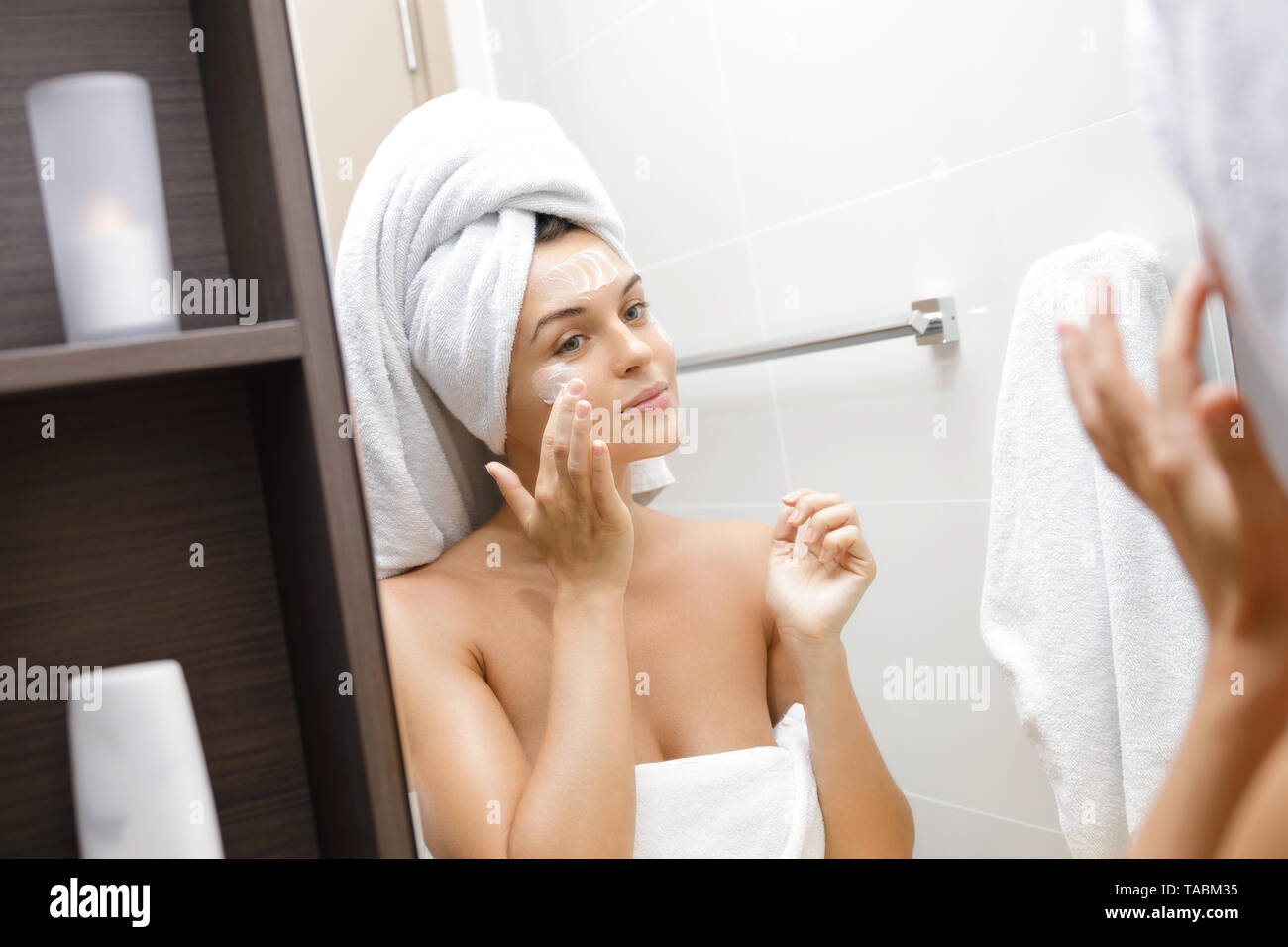 Beautiful young woman in bathroom with moisturizing and anti-aging cream applied on her face - Stock Image
