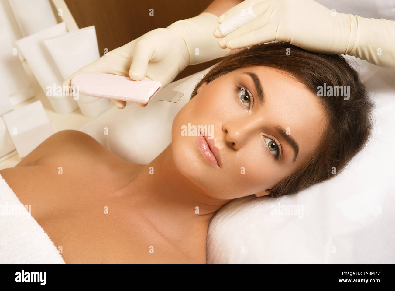 Beautiful woman in professional beauty spa salon during ultrasonic facial cleansing procedure - Stock Image
