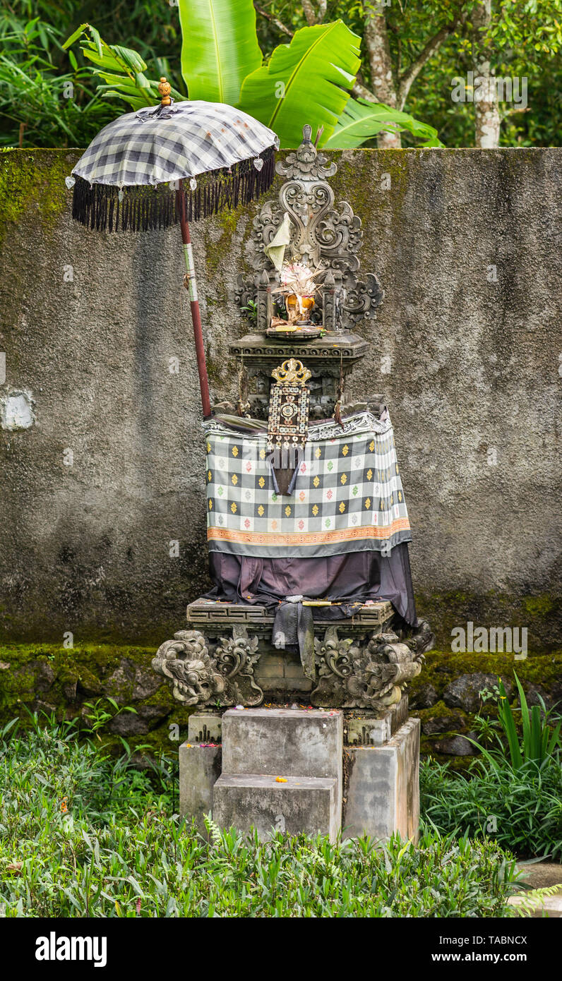 Bedugul, Bali, Indonesia - February 25, 2019: Hindu shrine in green garden along road set against gray molded wall. Drape with design of squares and s - Stock Image