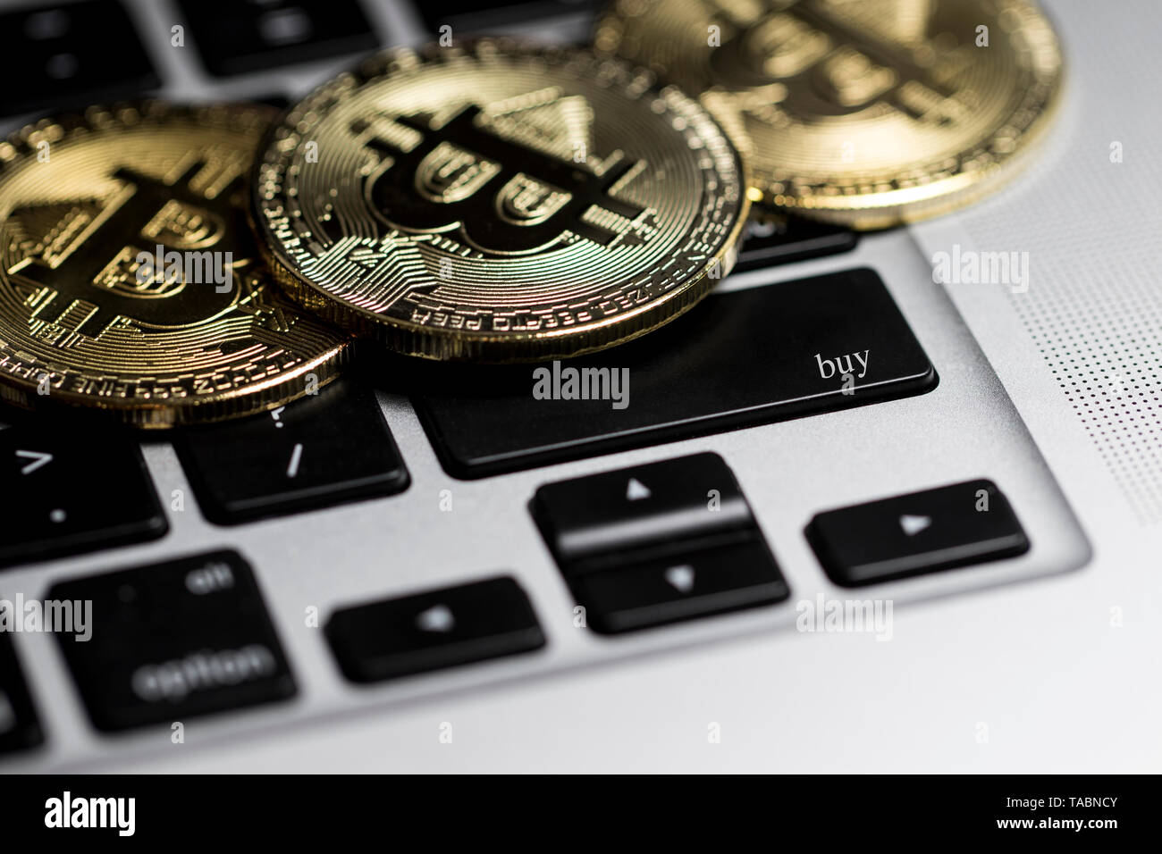 Crypto currencies buying and selling. Computer keyboard with Bitcoin coins on in. Buying and investing in digital currencies. Stock Photo