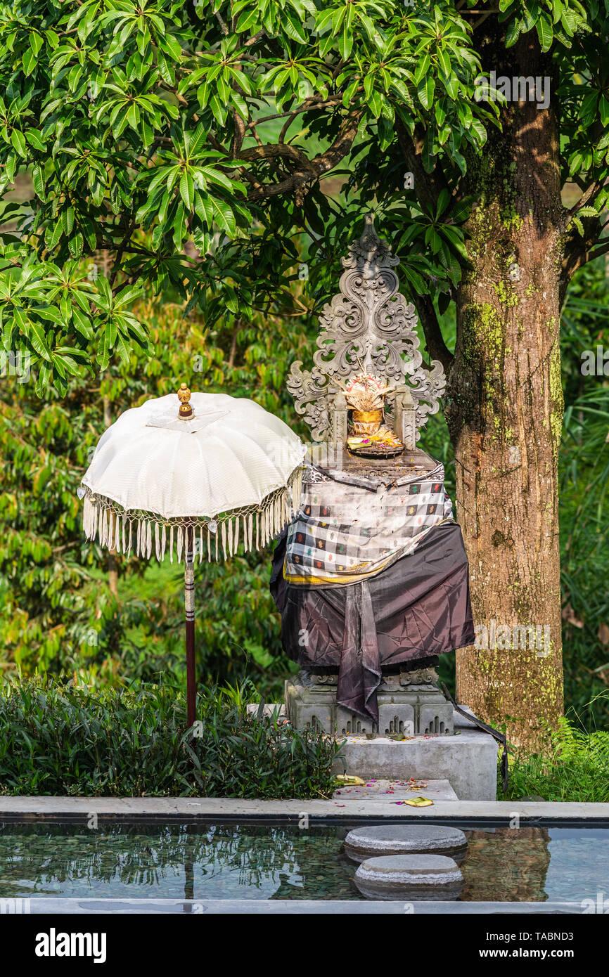 Bedugul, Bali, Indonesia - February 25, 2019: Hindu shrine behind pond in green garden along road set against green tree foliage. Drape with design of - Stock Image