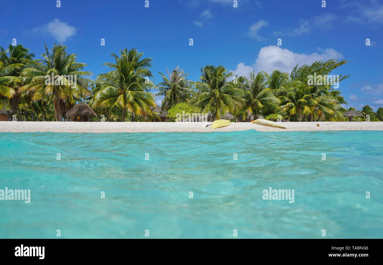 Tropical sea shore with kayaks on the beach and coconut trees with huts, seen from water surface, atoll of Tikehau, Tuamotu, French Polynesia, Pacific Stock Photo