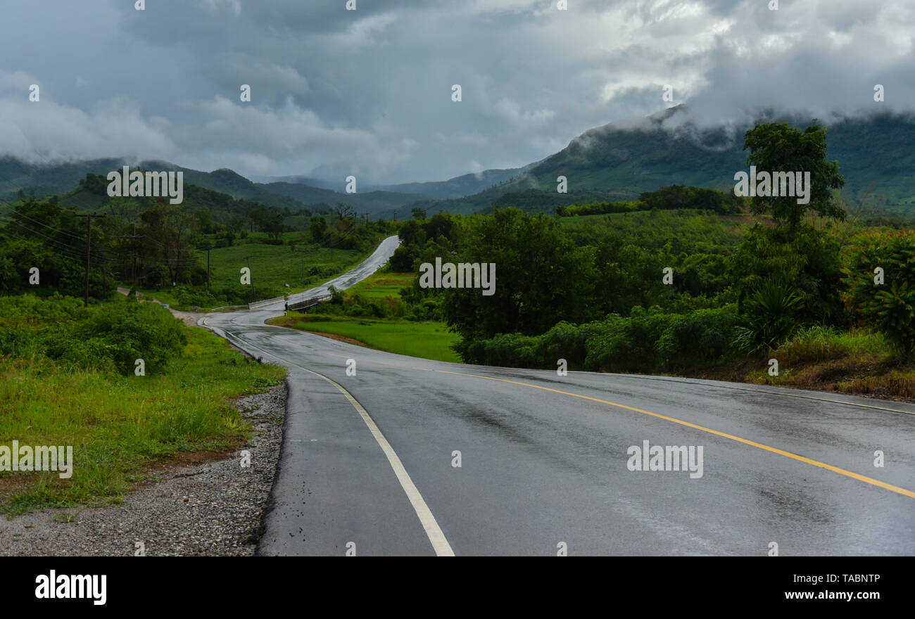 Slippery road / wet road curve to the mountain after rain with rain clouds cover - Stock Image