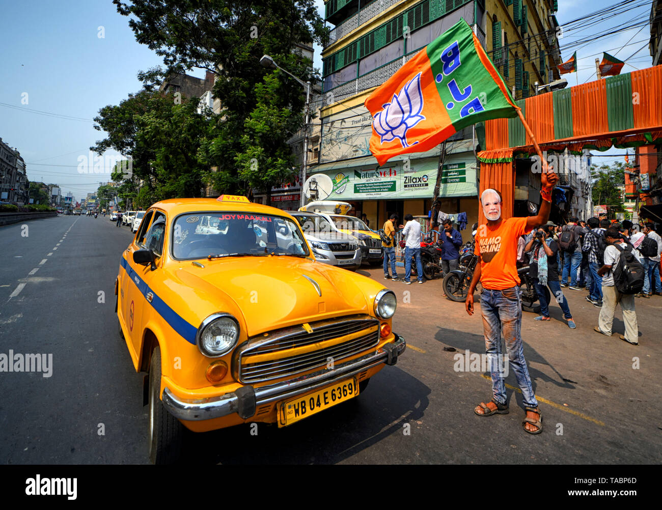 A supporter of Bharatiya Janata Party (BJP) seen wearing a Mask of Narendra Modi while weaving BJP Flags in front of the Party Head quarter in Kolkata after making massive Win in West Bengal & India election. Bharatiya Janata Party (BJP) wins election in Kolkata, India. - Stock Image