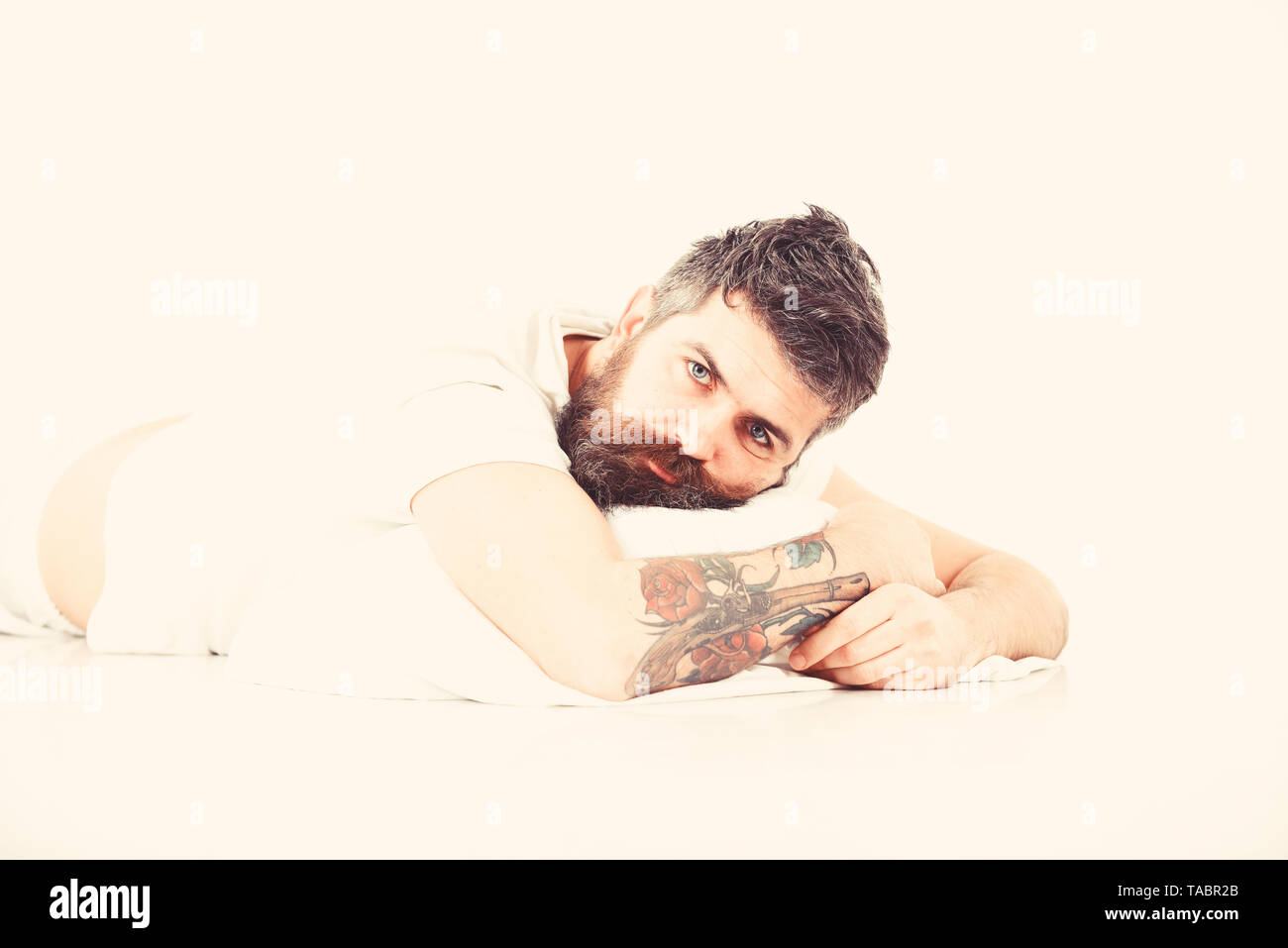 Hipster drowsy, wants to sleep. Hipster with beard not slept well. Man with sleepy face lies on pillow. Man with beard and mustache tired, white background. Bad slept concept. - Stock Image