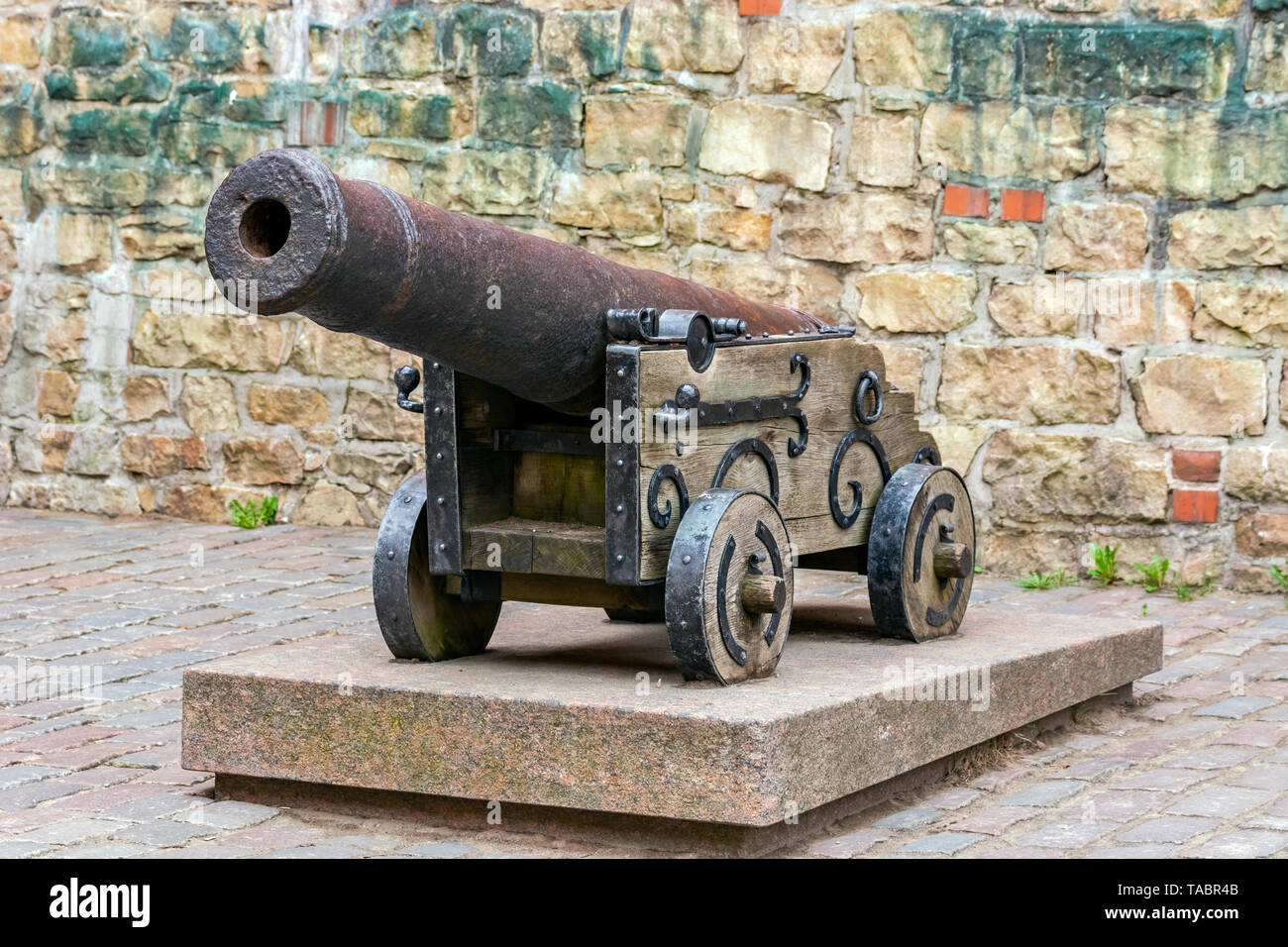 Old cast-iron cannon on a wooden carriage with wooden wheels, standing on a stone plate against the background of the fortress wall. - Stock Image