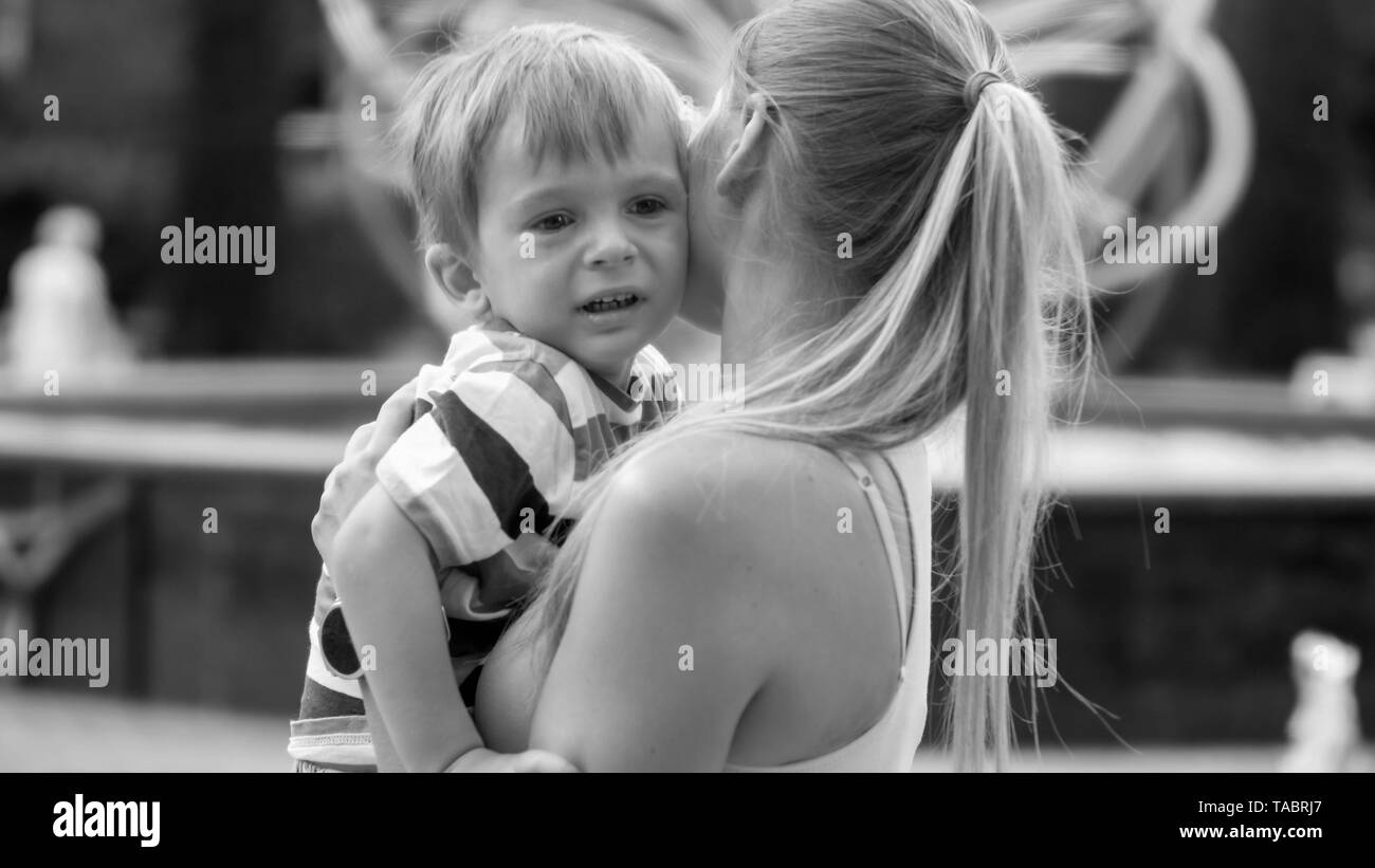 Black and white portrait of crying 3 years old toddler boy hugging his mother in park - Stock Image