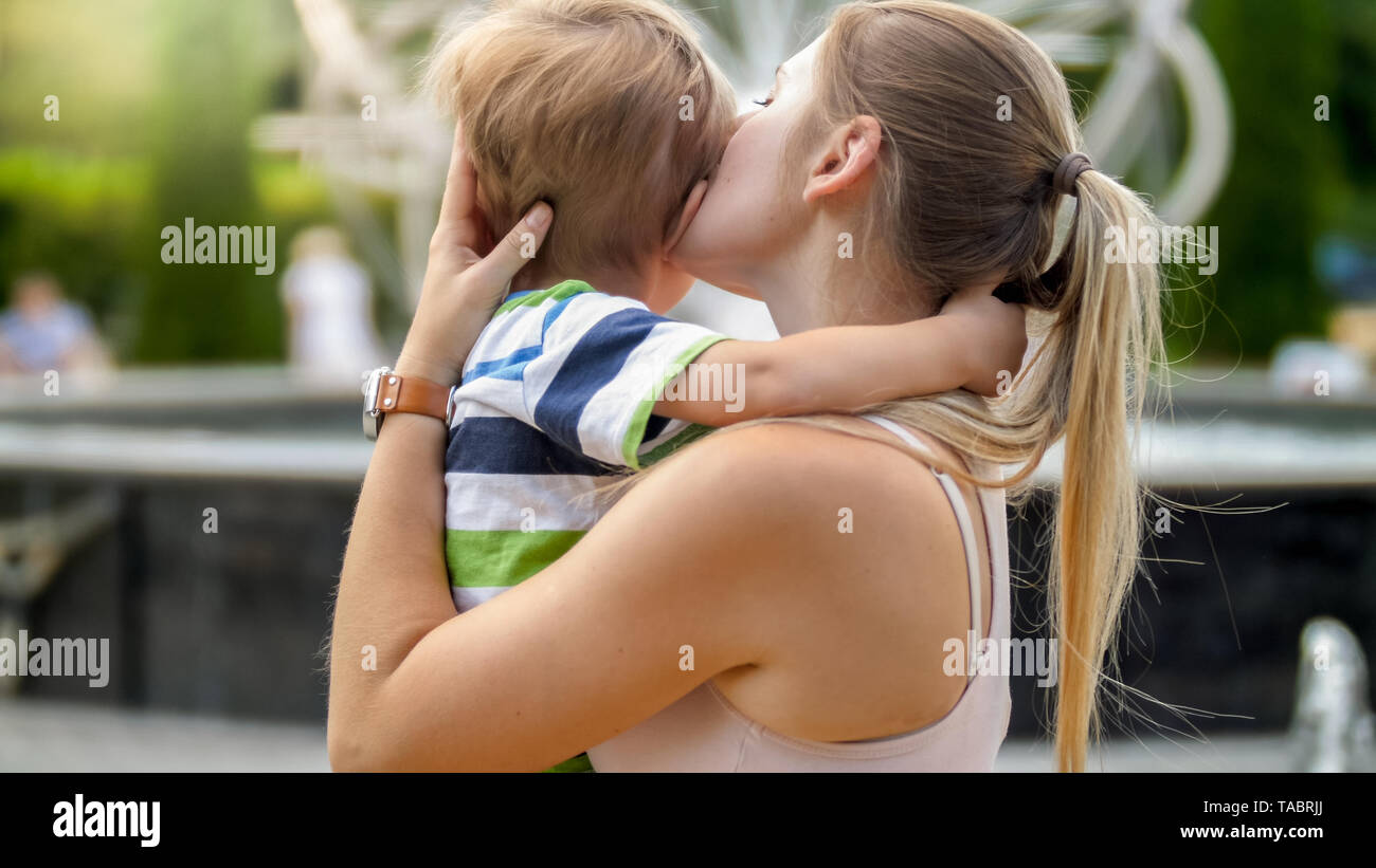 Closeup portrait of young mother hugging and caressing her crying little child boy in park - Stock Image