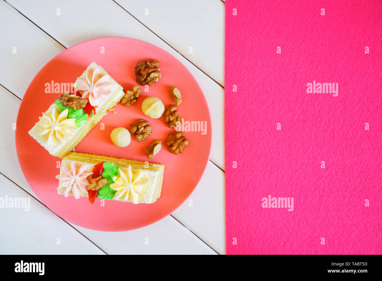 Slices of sponge cake with cream decorations, macadamia nuts and walnuts in a plate on a white and pink background. Wooden table and tablecloth. Dayli - Stock Image