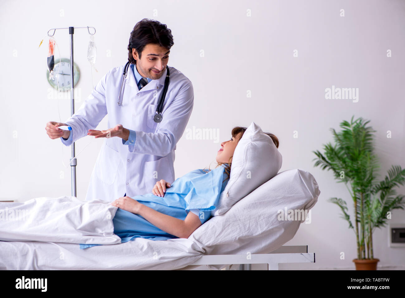 Male doctor visiting female patient in ward - Stock Image
