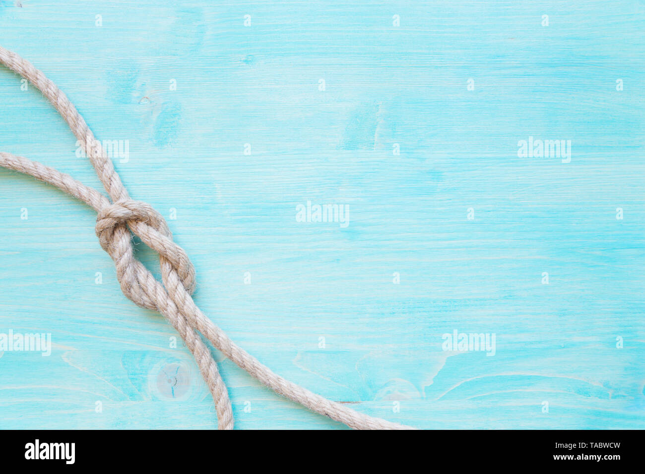 Rough hemp rope tied knot sea is on the background of blue faded wooden planks. Marine concept - Stock Image