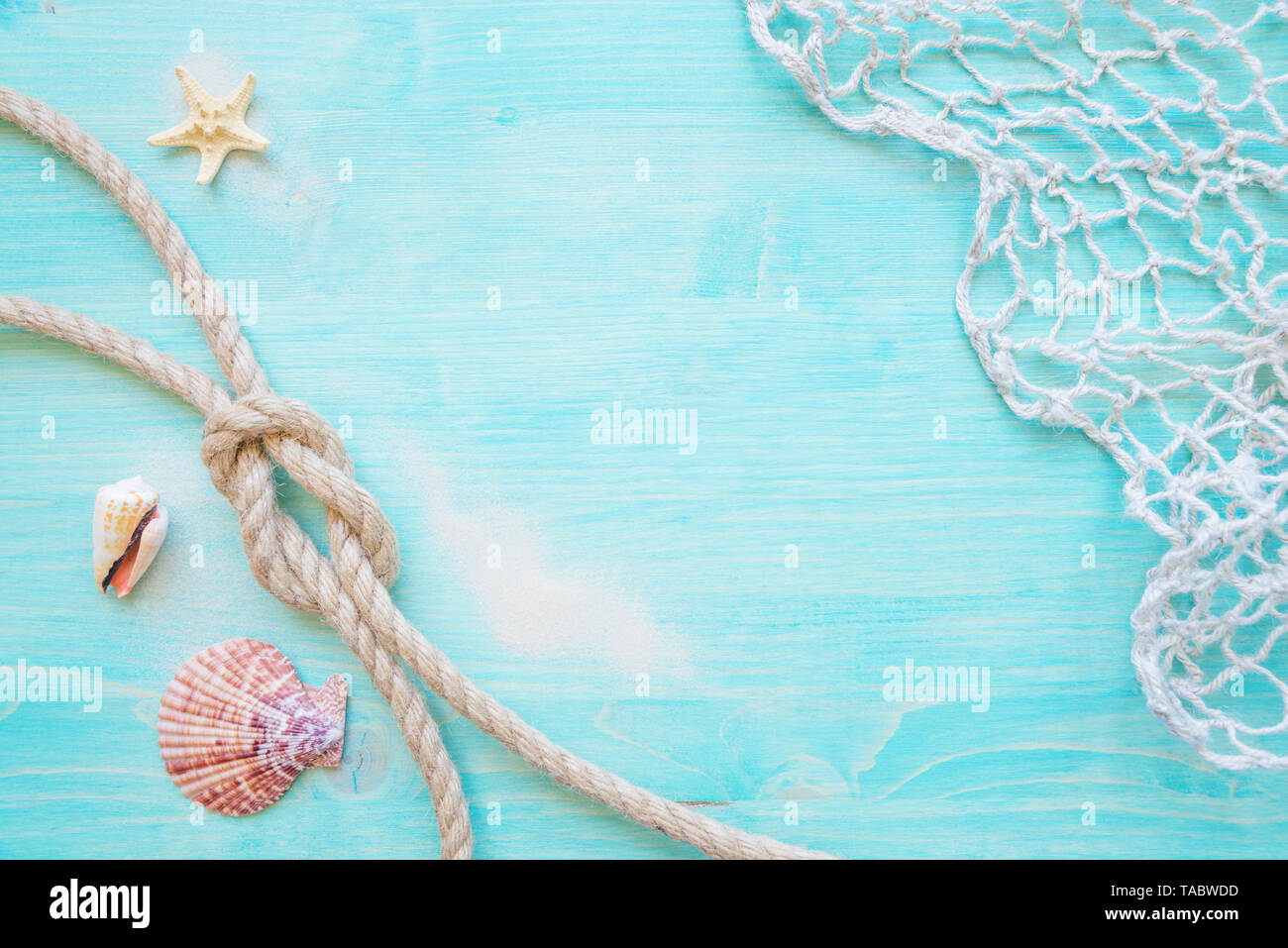 Rough hemp rope tied knot sea, hells, starfishes and fishing network are on the background of blue faded wooden deck. Marine concept - Stock Image