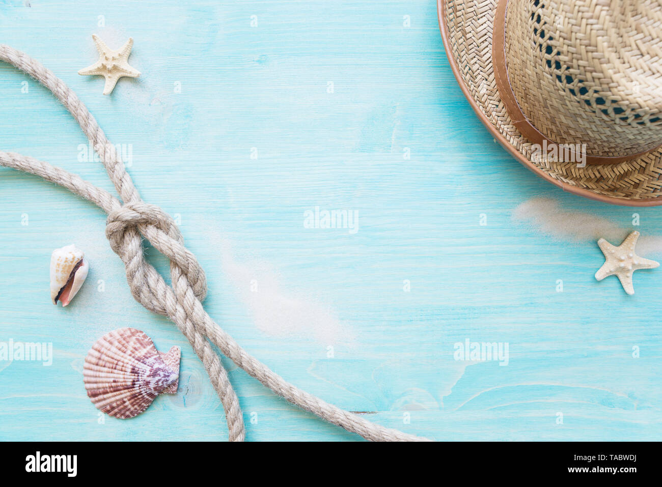 Rough hemp rope tied knot sea, hells, starfishes and straw hat are on the background of blue faded wooden deck. Marine concept - Stock Image