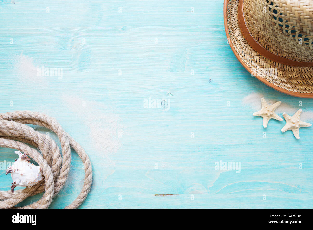 Rough hemp rope, shell, starfishes, white sea sand and straw hat are on the background of blue faded wooden deck. Marine concept - Stock Image
