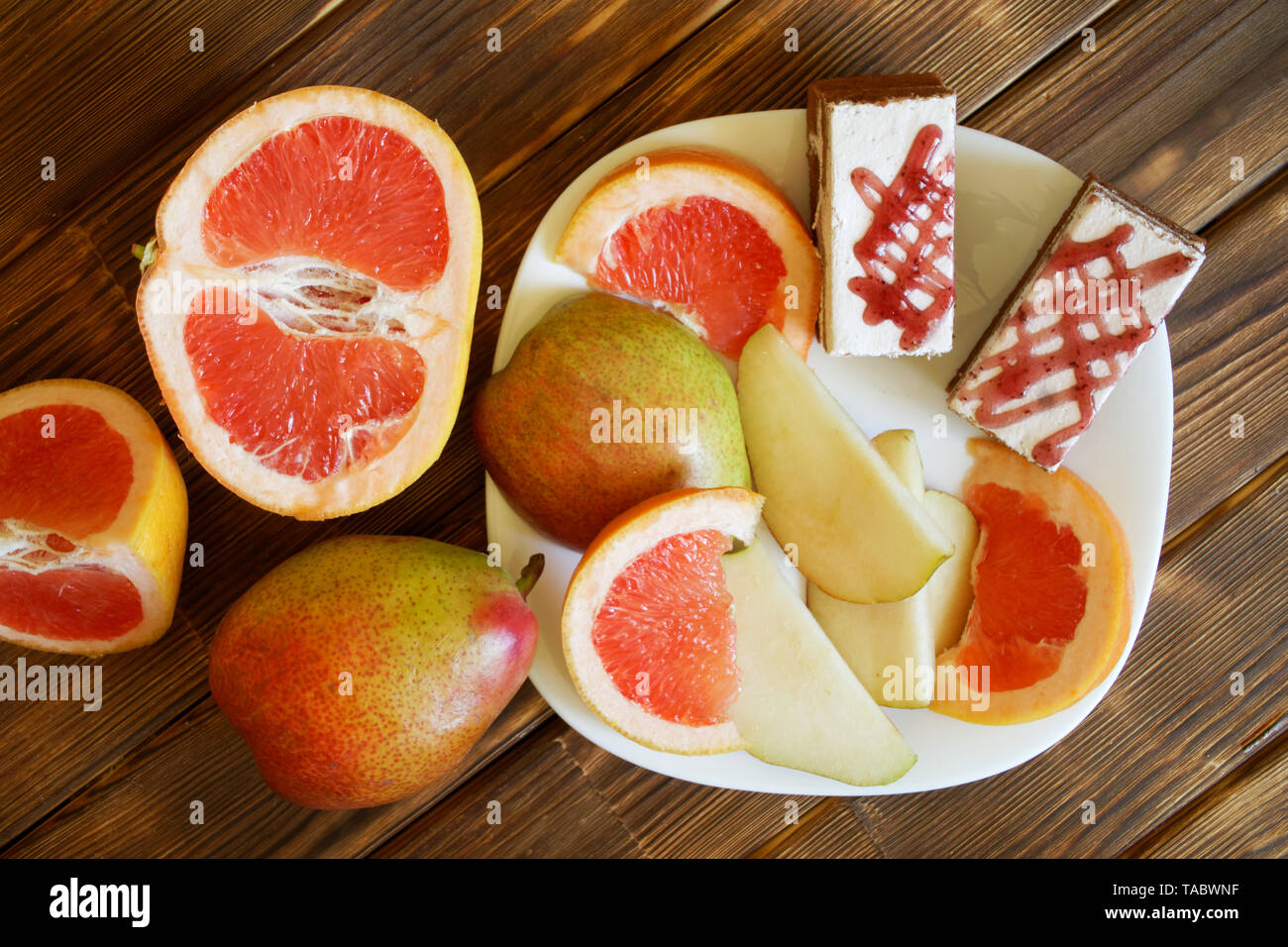 Sponge cakes and slices of grapefruit and pears lie in a white plate on a wooden surface made of pine boards. Buffet in authentic natural hotel. Dayli - Stock Image