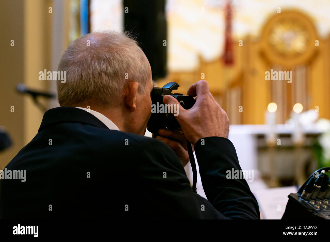 A gray-haired man in a suit takes pictures during church ceremonies. Shot from the back, blurry altar in the background. - Stock Image