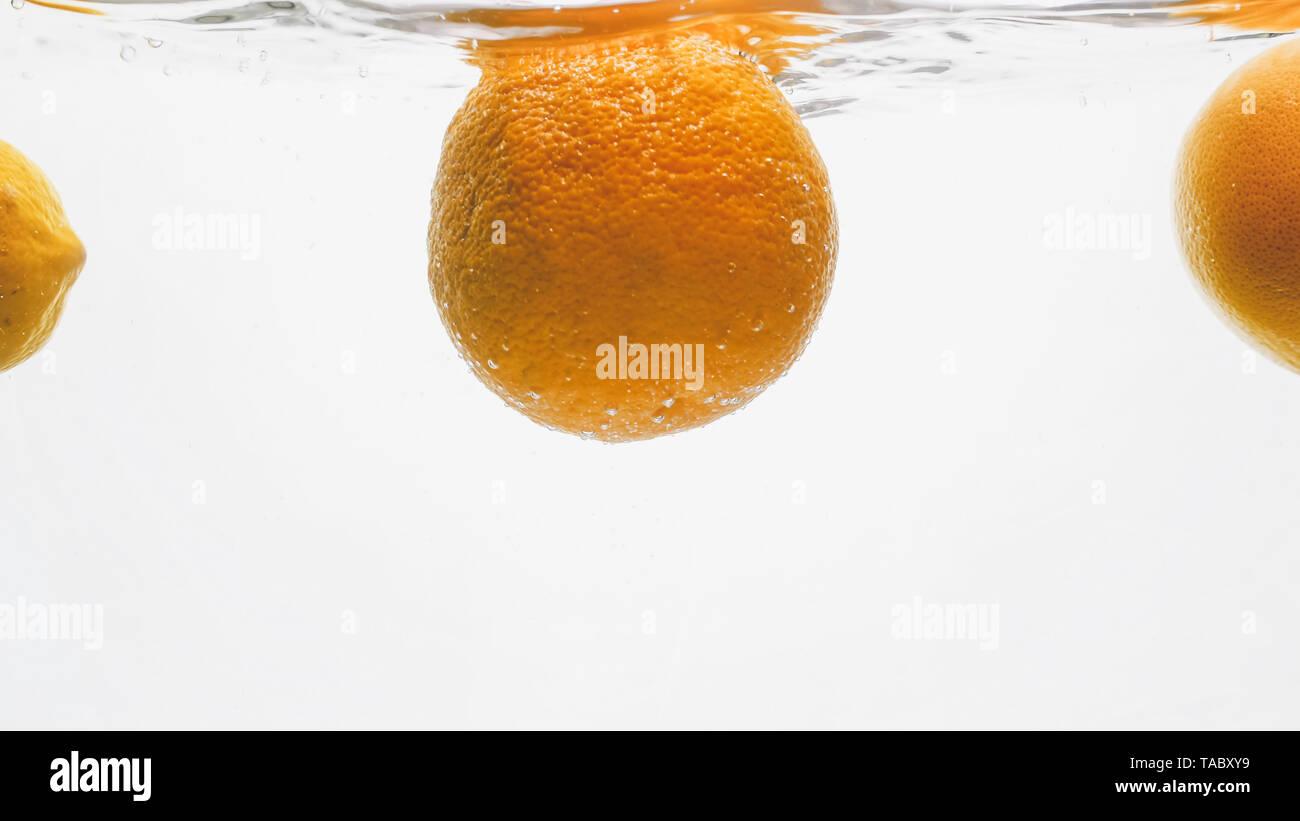 Closeup image of fresh juicy oranges falling in water. Tasty fruits splashing and floating on water surface - Stock Image