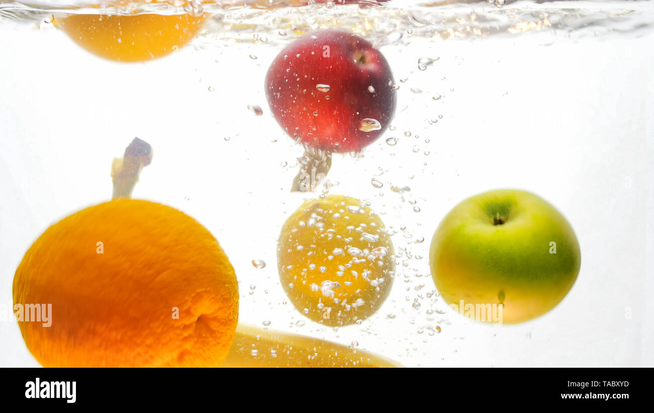 Closeup isolated image of fresh ripe apples, bananas and oranges falling and splashing in water - Stock Image