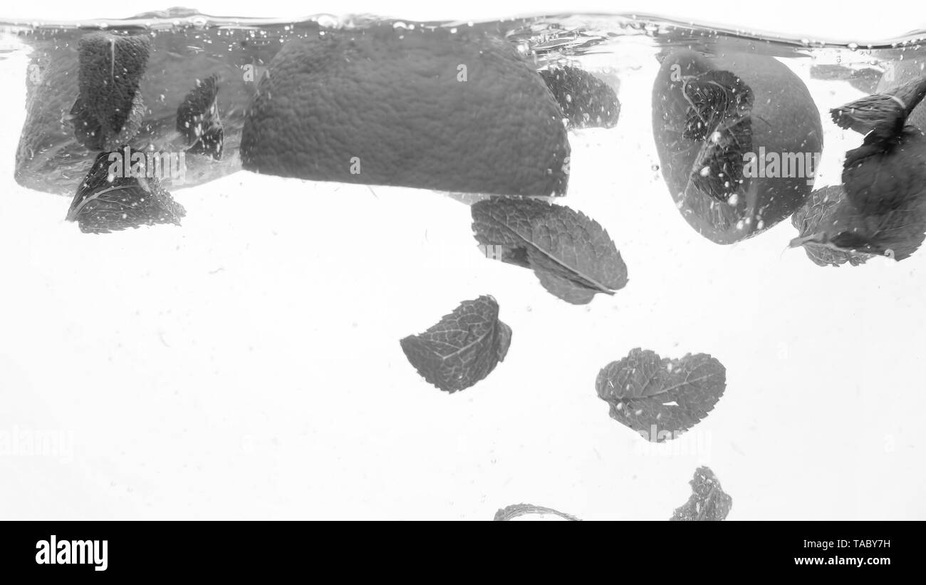 Black and white closeup image of oranges and mint leaves floating in water. Fruits falling and splashing water - Stock Image