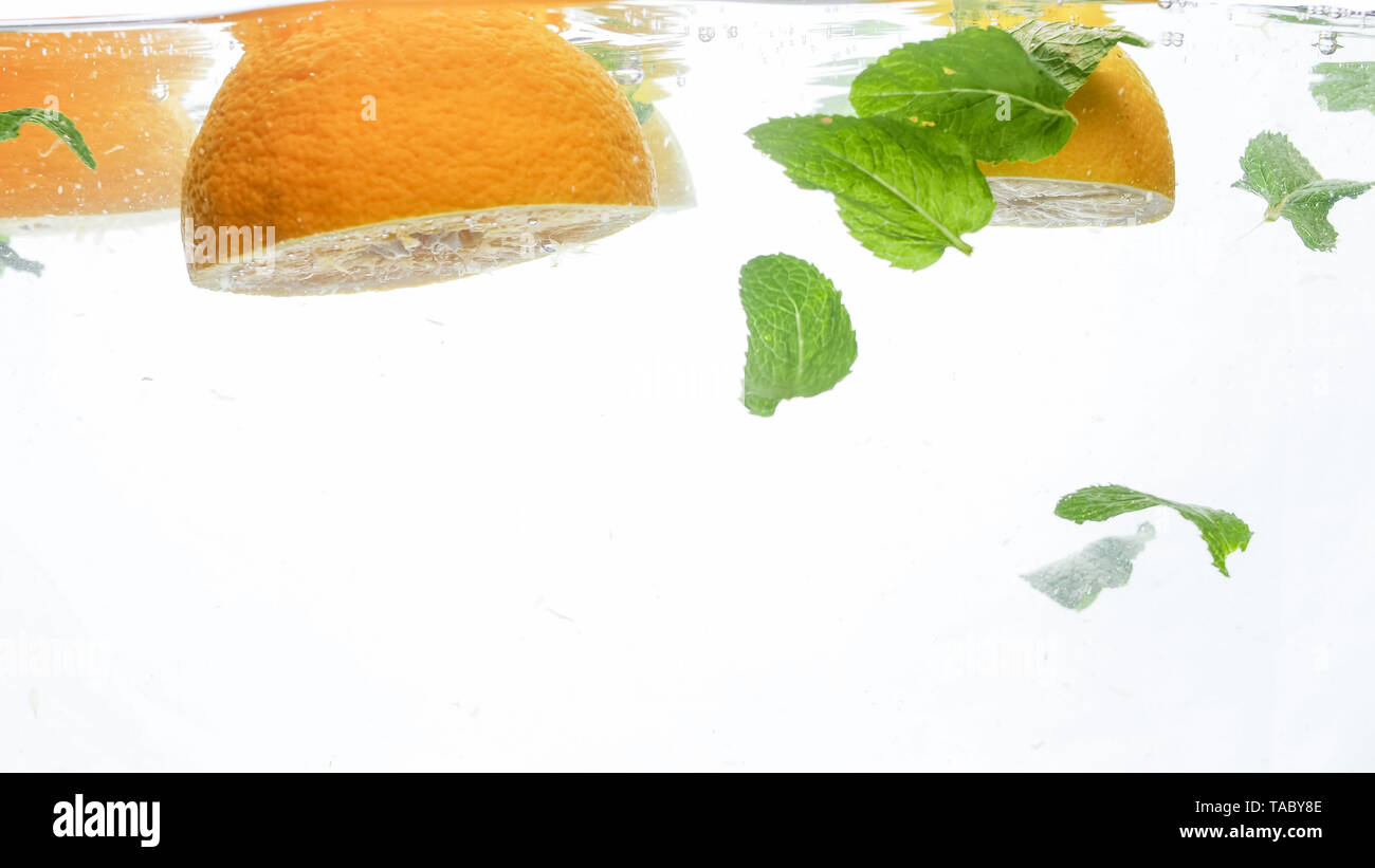 Closeup image of cut fresh juicy oranges with mint leaves floating in clear water against white background - Stock Image