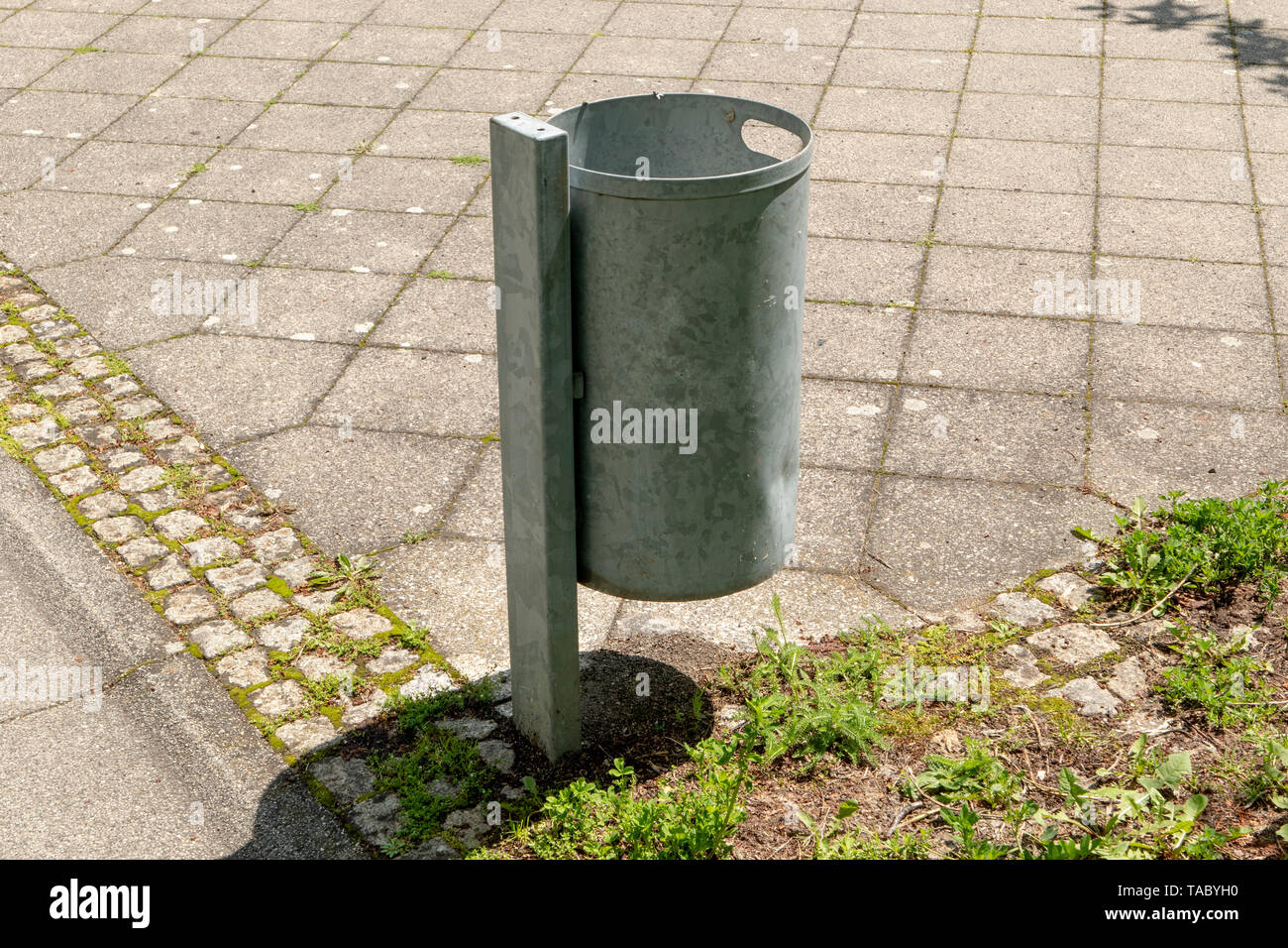 Metal rubbish bin in the park with lawn and paving stones - Stock Image