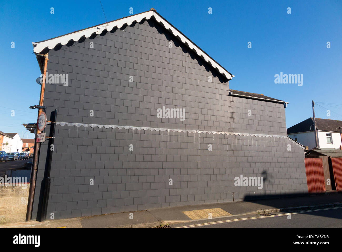 Recently installed weather proof cover / covering of (apparently artificial fibre cement slate) slate effect tiles / roof slates on a Victorian terraced house gable end. (99) - Stock Image