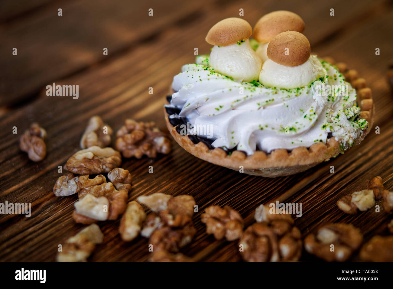 Cake, made in the form of a basket with cream and imitation of mushrooms, lies on a wooden table next to peeled walnuts. Shallow depth of field. Dayli - Stock Image