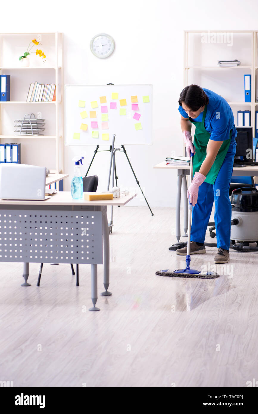 Male handsome professional cleaner working in the office - Stock Image