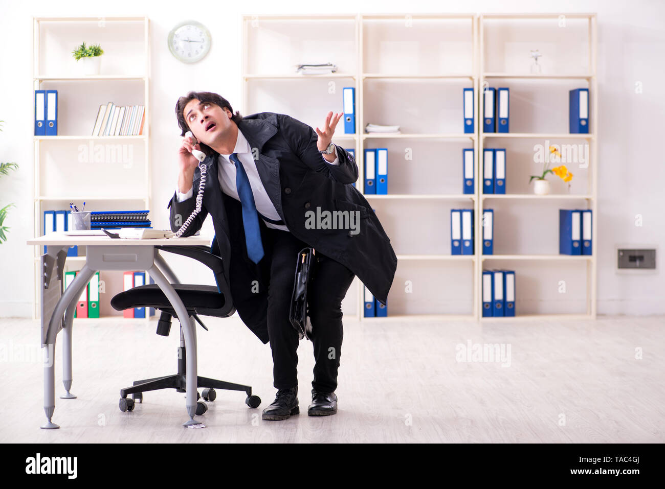 Young male employee in the office in time management concept - Stock Image