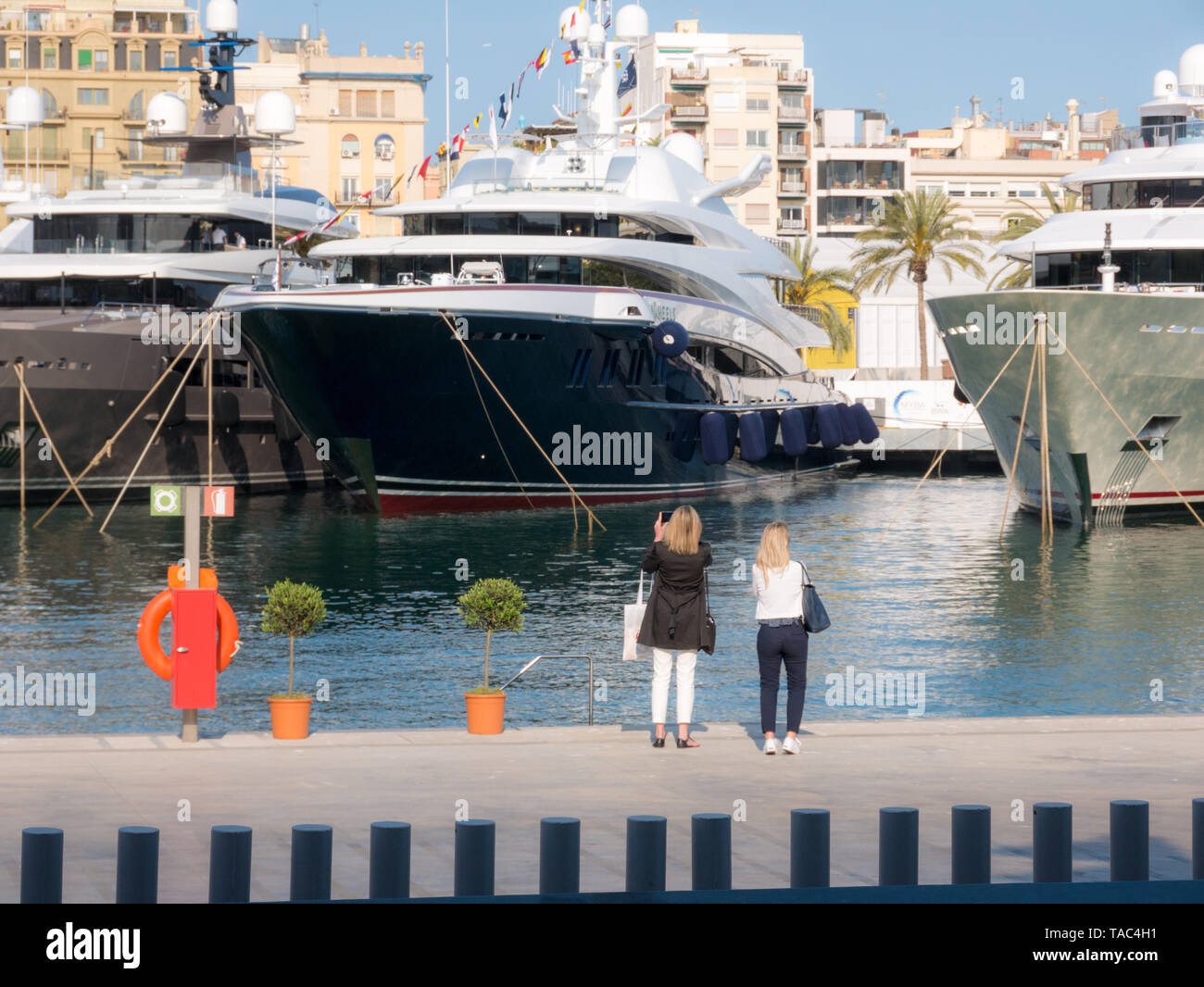 Two women taking luxury yachts in picture - Stock Image