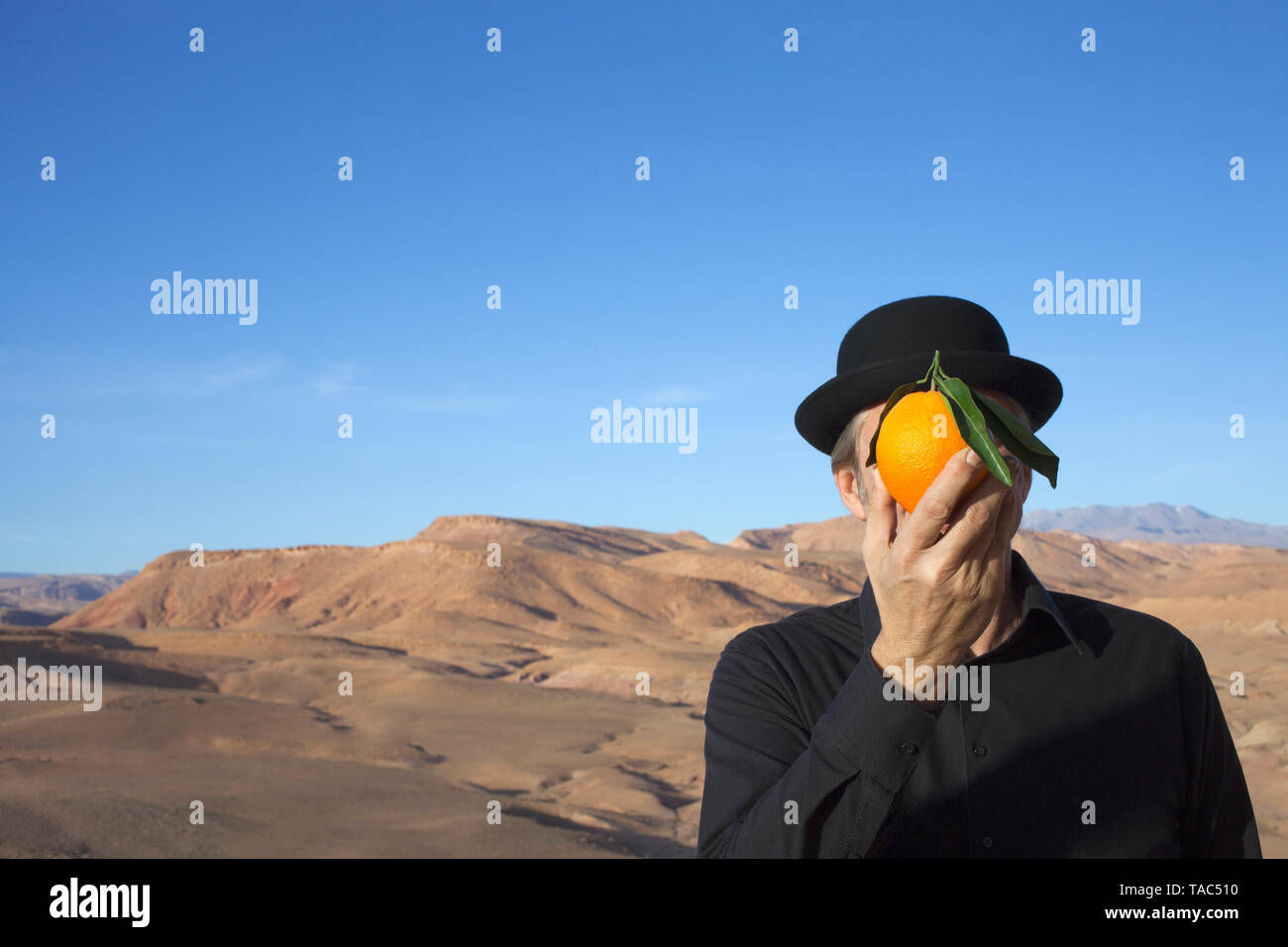 Morocco, Ounila Valley, man wearing a bowler hat holding an orange in front of his face - Stock Image
